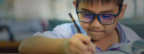 Boy with glasses writing